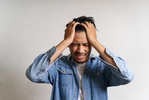 De jonge aziatische mens legde handen op zijn hoofd. hij voelt zich ziek en heeft hoofdpijn door problemen te hebben.