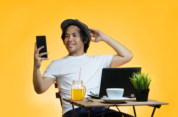 De jonge aziatische mens neemt een selfie terwijl het werken aan de zomervakantie tegen gele achtergrond