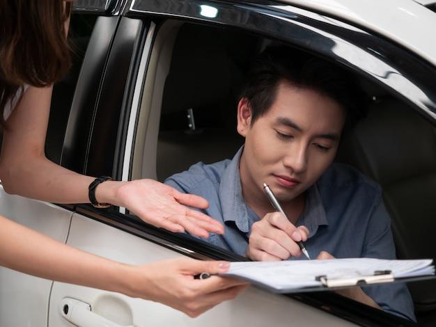 De jonge aziatische mens spreekt met afdelingschef terwijl het kiezen van een auto in handel drijven.