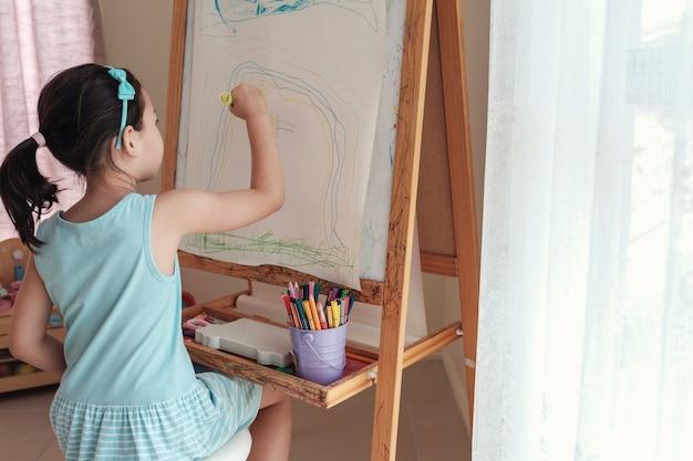 De jonge aziatische regenboog van de meisjestekening op schildersezel, montessori homeschool onderwijs