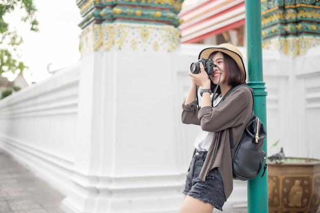 De jonge aziatische reisvrouw geniet van met mooie plaats in bangkok