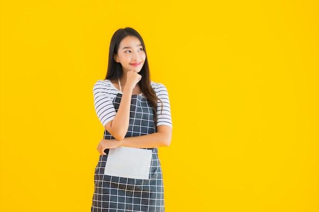 De jonge aziatische schort van de vrouwenslijtage met gelukkige glimlach
