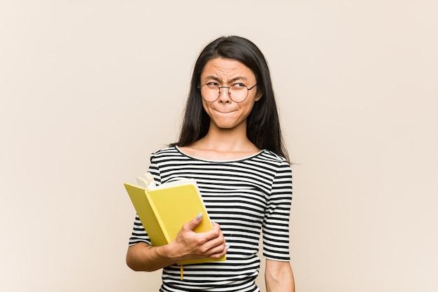 De jonge aziatische studente die een boek verward houden, voelt twijfelachtig en onzeker.