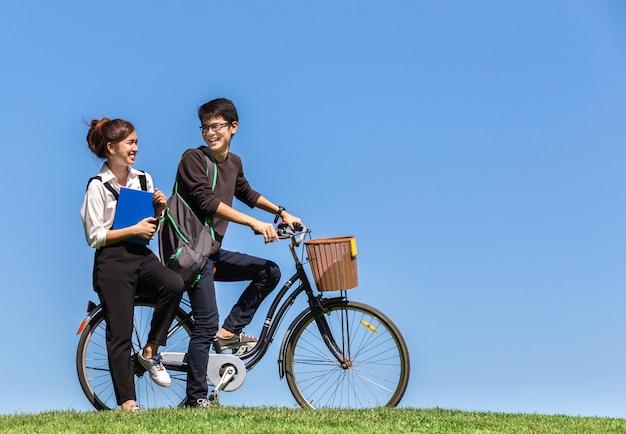 De jonge aziatische studenten berijden een fiets op universiteit met aardbedelaars