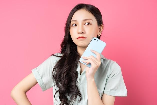 De jonge aziatische telefoon van de vrouwenholding in haar hand met peinzende blik op roze