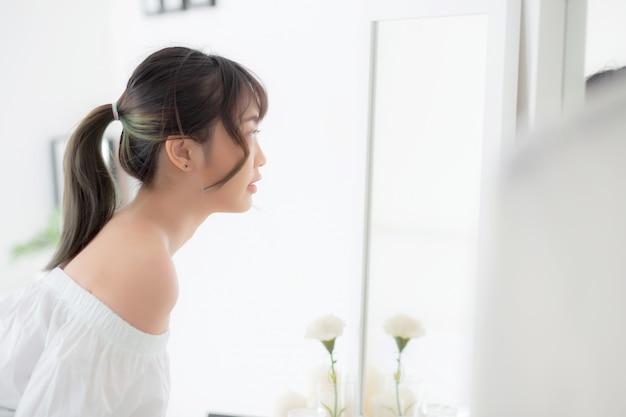 De jonge aziatische vrouw bekijkt spiegel