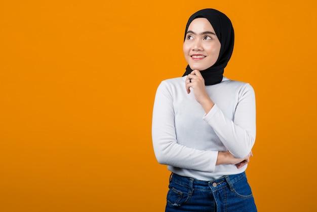 De jonge aziatische vrouw denkt en kijkt gelukkig