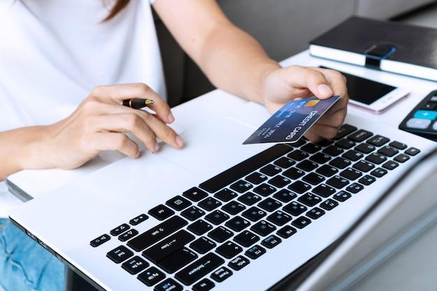 De jonge aziatische vrouw die computerlaptop met behulp van terwijl thuis het houden van creditcard, sluit omhoog
