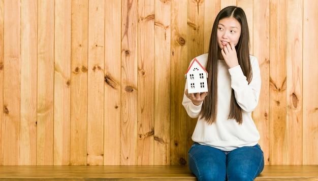 De jonge aziatische vrouw die een huispictogram houden ontspande het denken over iets bekijkend een exemplaarruimte.