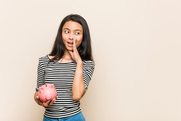 De jonge aziatische vrouw die een spaarvarken houdt zegt een geheim heet remmend nieuws en kijkt opzij