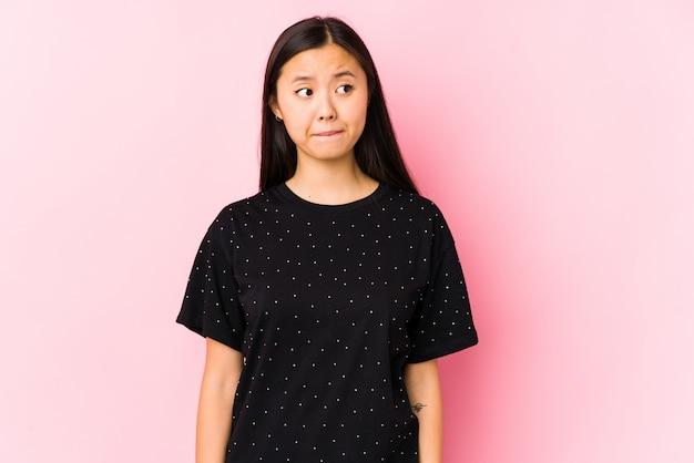De jonge aziatische vrouw die elegante geïsoleerde kleren dragen verward, voelt twijfelachtig en onzeker.