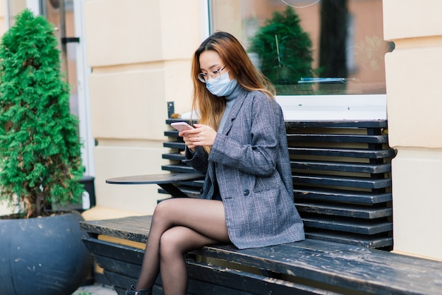 De jonge aziatische vrouw die gezichtsmasker draagt, staat bij een binnenlandse straat. nieuwe normale covid-19-epidemie