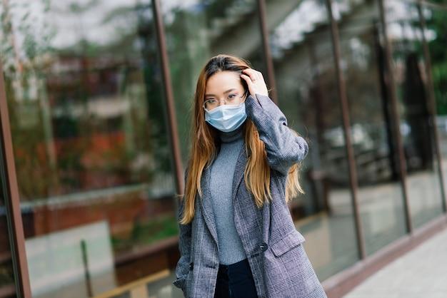 De jonge aziatische vrouw die gezichtsmasker draagt, staat in een binnenlandse straat. nieuwe normale covid-19-epidemie