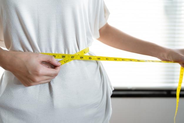 De jonge aziatische vrouw die maatregelenband gebruiken die haar taille meten na probeert gewicht te verliezen met eet gezond voedsel.