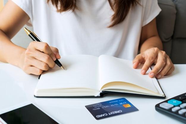 De jonge aziatische vrouw die op notitieboekje schrijven terwijl thuis het zitten in de woonkamer, sluit omhoog