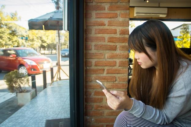 De jonge aziatische vrouw die slimme telefoon in winkel gebruiken, bedrijfstechnologie verbindt