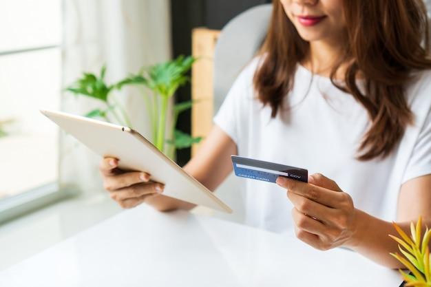 De jonge aziatische vrouw die tablet gebruiken terwijl thuis het houden van creditcard in de woonkamer, sluit omhoog