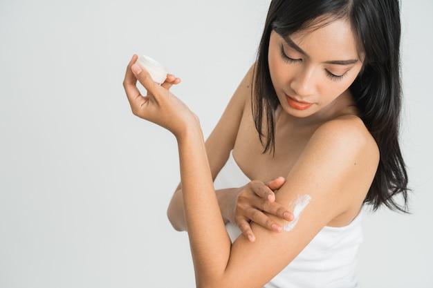 De jonge aziatische vrouw die van de huidzorg bodylotion op arm en schouder toepast