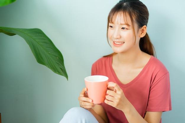 De jonge aziatische vrouw drinkt 's ochtends koffie