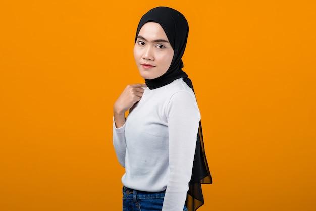 De jonge aziatische vrouw glimlacht en kijkt gelukkig terwijl hijab draagt