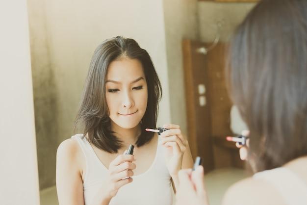 De jonge aziatische vrouw maakt omhoog zelf