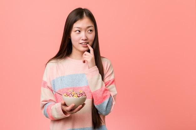 De jonge aziatische vrouw met een graangewassenkom ontspande het denken over iets bekijkend een exemplaarruimte.