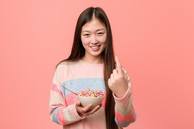 De jonge aziatische vrouw met een graangewassenkom richt met vinger op u alsof uitnodigend dichterbij kom.
