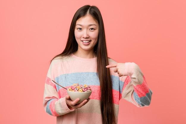 De jonge aziatische vrouw met een graankom werpt verrast richtend op zich, breed glimlachend.
