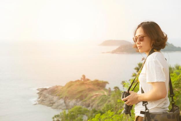 De jonge aziatische vrouw met in hand camera bekijkt mening van eiland en overzees.