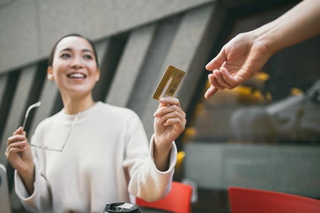 De jonge aziatische vrouw met in hand glazen zit buiten een koffiewinkel die voor koffie of thee betalen en laptop met behulp van