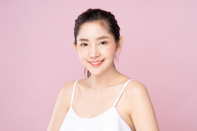 De jonge aziatische vrouw met schone verse witte huid met smileygezicht in schoonheid stelt