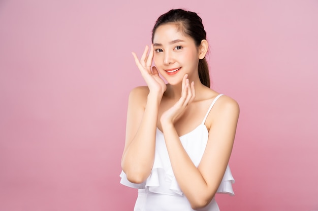 De jonge aziatische vrouw met schone verse witte huid wat betreft haar eigen gezicht zacht in schoonheid stelt