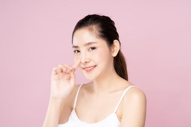 De jonge aziatische vrouw met schone verse witte huid wat betreft haar eigen neus zacht in schoonheid stelt
