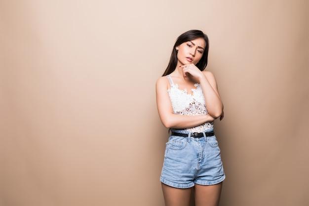 De jonge aziatische vrouw met vraagt gezicht dat op beige muur wordt geïsoleerd