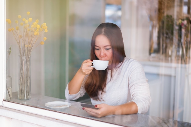 De jonge aziatische vrouw ontspant het drinken koffie, gebruikend telefoon. geschoten door een glazen raam in de coffeeshop.
