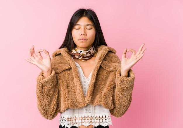 De jonge aziatische vrouw ontspant na harde werkdag, voert zij yoga uit.