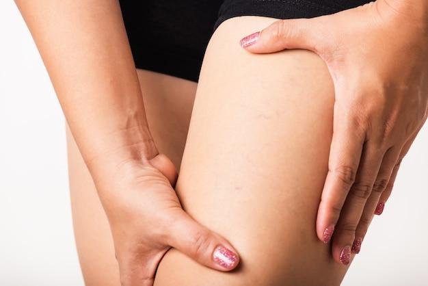 De jonge aziatische vrouw van de close-up heeft kramp in de benen van de kuit vermoeide pijn