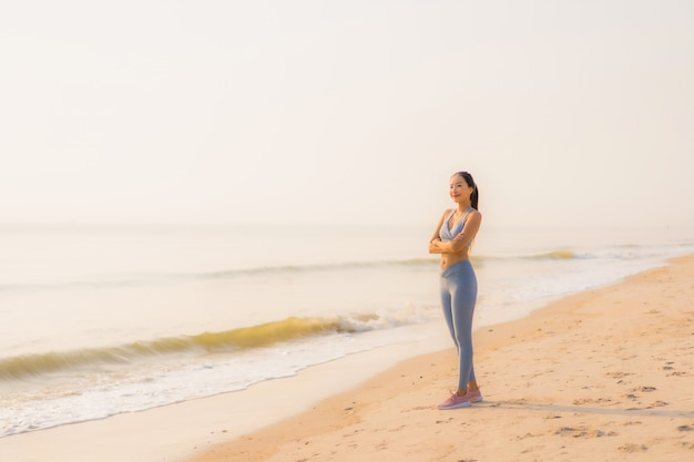 De jonge aziatische vrouw van de portretsport bereidt oefening voor of loopt op de strand overzeese oceaan