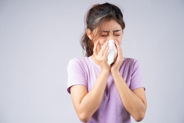 De jonge aziatische vrouw veegt haar neus met een tissue af