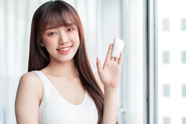 De jonge aziatische vrouw verwijderde make-up bij het raam