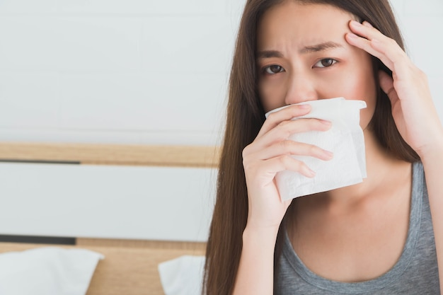 De jonge aziatische vrouw voelt hoofdpijnen en ongemak op bed in witte slaapkamerochtend.
