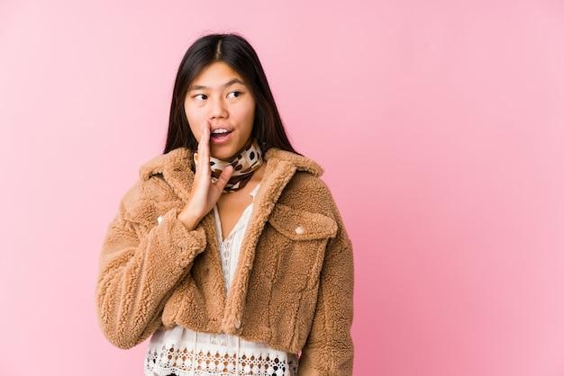 De jonge aziatische vrouw zegt een geheim heet remmend nieuws en kijkt opzij