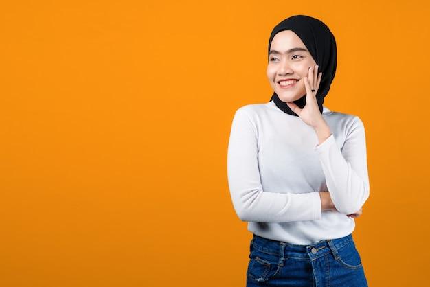 De jonge aziatische vrouw ziet er gelukkig en opgewekt uit op gele achtergrond
