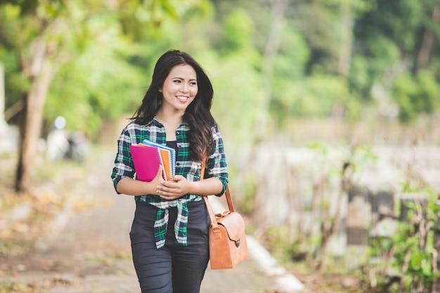 De jonge aziatische vrouwelijke studentenholding boekt terwijl het lopen op de pa