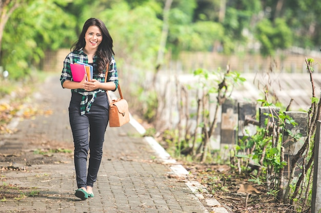 De jonge aziatische vrouwelijke studentholding boekt terwijl het lopen op het park