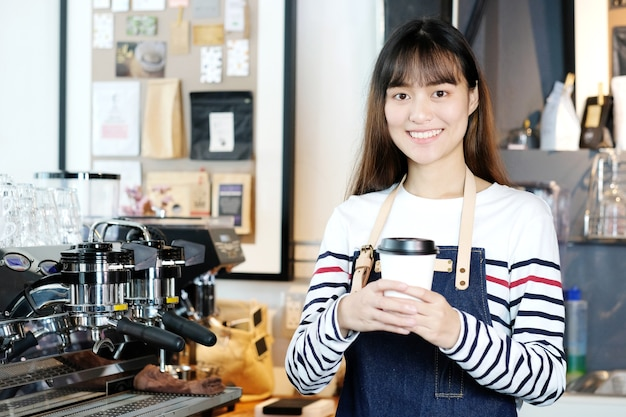 De jonge aziatische vrouwen barista die a houden haalt koffiekop weg.