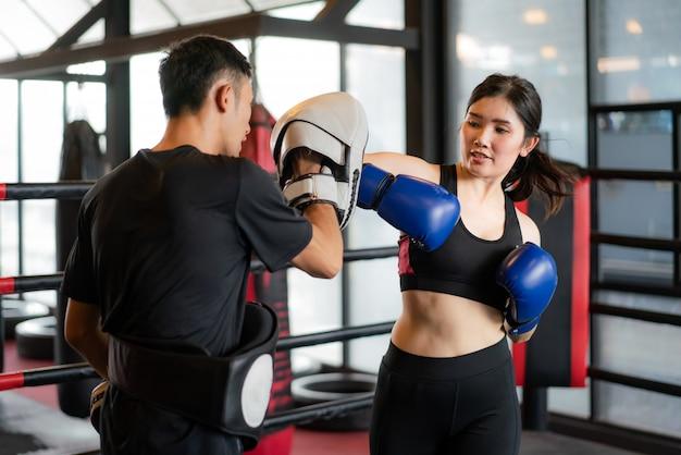 De jonge aziatische vrouwenbokser slaat met een elleboog aan professionele trainer in in dozen doend stadion