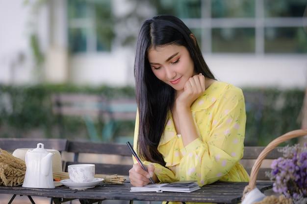 De jonge aziatische vrouwenhand schrijft op blocnote met een pen in de tuin