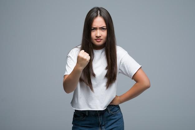 De jonge aziatische vuist van de vrouwengreep omhoog op grijze achtergrond