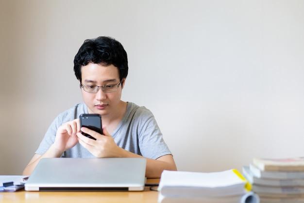 De jonge aziatische zakenman ontspant binnen toevallig tijdens het werken vanuit huis